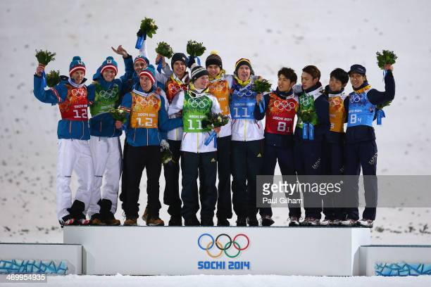 Silver medalists Austria gold medalists Germany and bronze medalists Japan celebrate during the flower ceremony for the Men's Team Ski Jumping final...