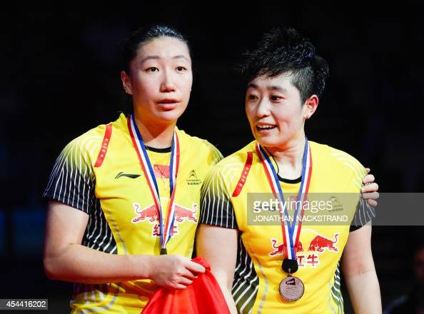 Silver medalists China's Wang Xiaoli and Yu Yang celebrate on the podium after the women's double final match at the 2014 BWF Badminton World...