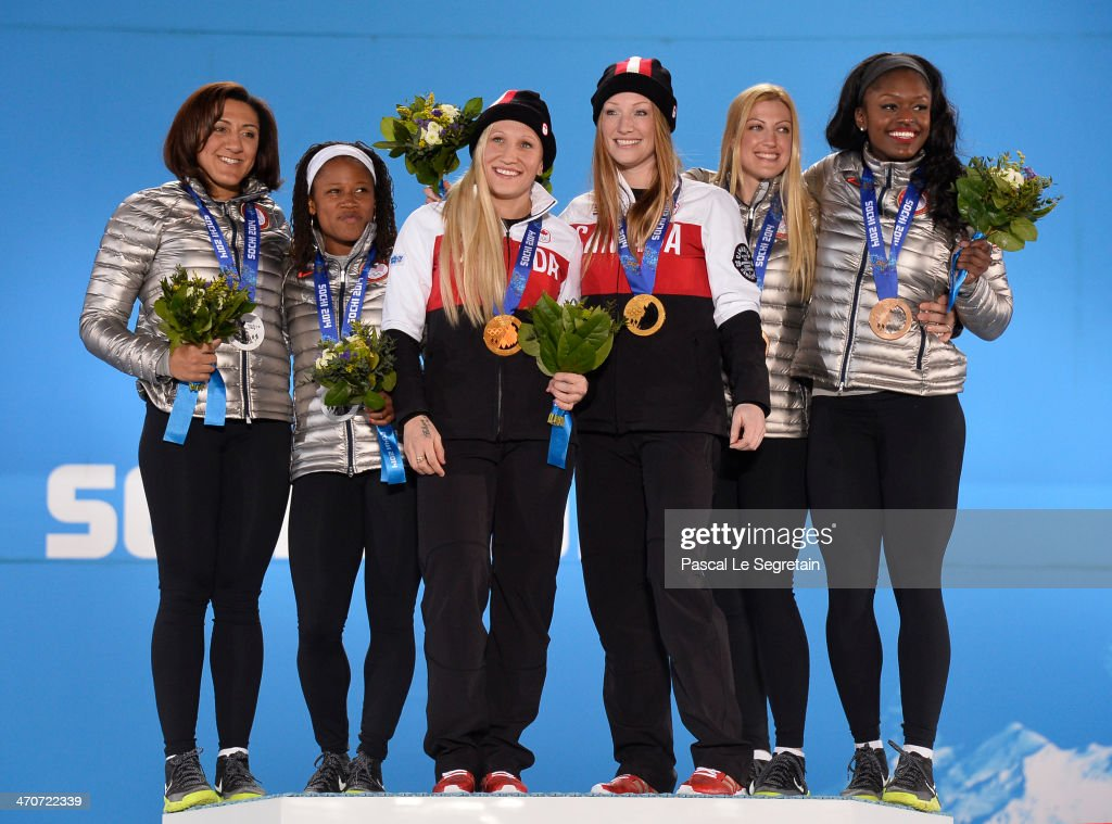 Silver medalists Elana Meyers and Lauryn Williams of the United States team 1, gold medalists Kaillie Humphries and Heather Moyse of Canada team 1 and bronze medalists Jamie Greubel and Aja Evans of the United States team 2 celebrate on the podium during the medal ceremony for the Women's Bobsleigh on day thirteen of the Sochi 2014 Winter Olympics at at Medals Plaza on February 20, 2014 in Sochi, Russia.