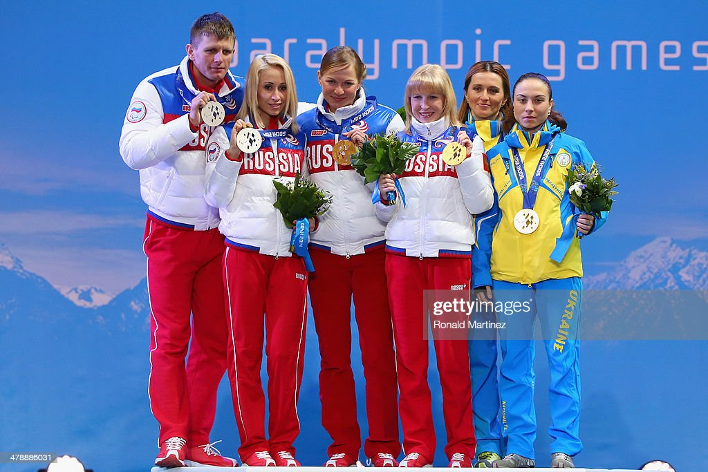 Silver medalists guide Alexey Ivanov and Mikhalina Lysova of Russia, Iuliia Budaleeva of Russia (R) and guide Tatiana Maltseva (L) sing the national anthem as bronze medalists guide Lada Nesterenko and Oksana Shyshkova of the Ukraine pose at the medal ceremony for the the Women's 12.5km Visually Impaired Biathlon on day eight of the Sochi 2014 Paralympic Winter Games at Laura Cross-country Ski & Biathlon Center on March 15, 2014 in Sochi, Russia.