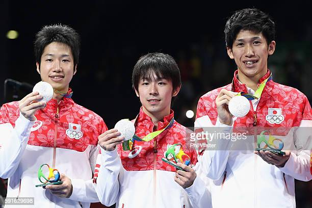 Silver medalists Jun Mizutani Maharu Yoshimura and Koki Niwa of Japan celebrate during the medal ceremony after the Men's Team Table Tennis gold...