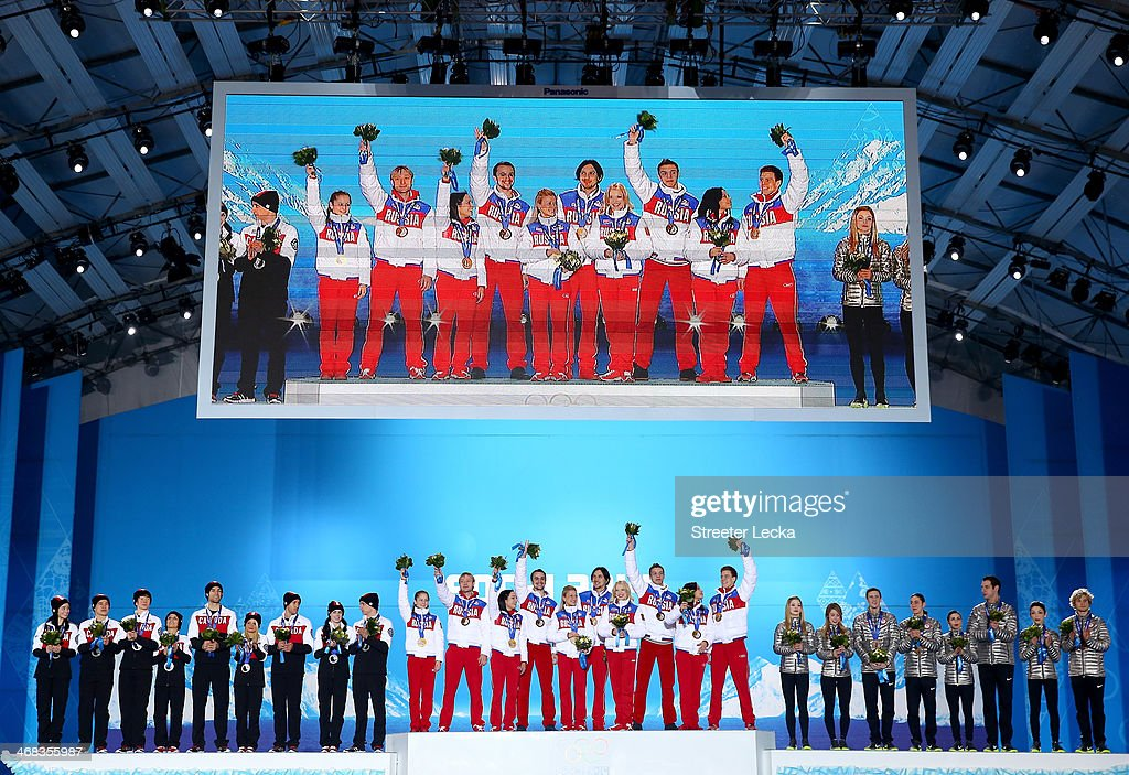 Silver medalists Kaetlyn Osmond, Patrick Chan, Kevin Reynolds, Meagan Duhamel, Eric Radford, Kirsten Moore-Towers, Dylan Moscovitch, Tessa Virtue and Scott Moir of Canada, gold medalists Yulia Lipnitskaya, Evgeny Plyushchenko, Ksenia Stolbova, Fedor Klimov, Tatiana Volosozhar, Maxim Trankov, Ekaterina Bobrova, Dmitri Soloviev, Elena Ilinykh and Nikita Katsalapov of Russia and bronze medalists Gracie Gold, Ashley Wagner, Jeremy Abbott, Jason Brown, Maria Castelli, Simon Shnapir, Meryl Davis and Charlie White of the United States celebrate during the medal ceremony for the Team Figure Skating Overall during the medal ceremony on day 3 of the Sochi 2014 Winter Olympics at Medals Plaza in the Olympic Park on February 10, 2014 in Sochi, Russia.
