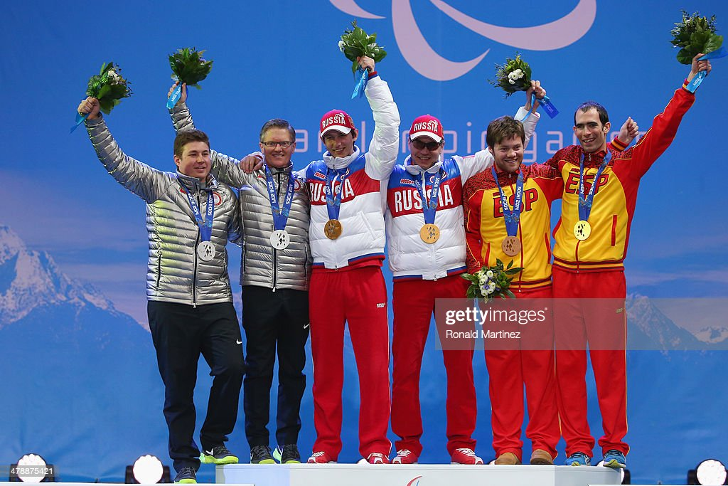 Silver medalists Mark Bathum (R) of the United States and guide Cade Yamamoto (L), Gold medalists Valerii Redkozubov (R) of Russia and guide Evgeny Geroev (L) and Gabriel Juan Gorce Yepes (R) of Spain and guide Josep Arnau Ferrer Ventura (L) celebrate at the medal ceremony for men's Super Combined Visually Impaired on day eight of the Sochi 2014 Paralympic Winter Games at Laura Cross-country Ski & Biathlon Center on March 15, 2014 in Sochi, Russia.