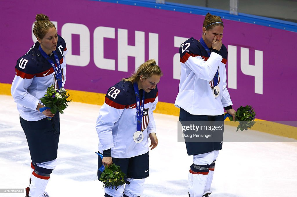 Silver medalists Meghan Duggan #10, Amanda Kessel #28 and Kacey Bellamy #22 of the United States react during the flower ceremony after losing 3-2 to Canada in overtime during the Ice Hockey Women's Gold Medal Game on day 13 of the Sochi 2014 Winter Olympics at Bolshoy Ice Dome on February 20, 2014 in Sochi, Russia.
