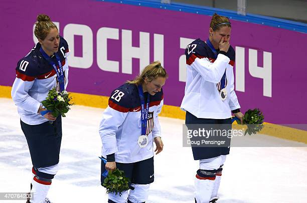 Silver medalists Meghan Duggan Amanda Kessel and Kacey Bellamy of the United States react during the flower ceremony after losing 32 to Canada in...