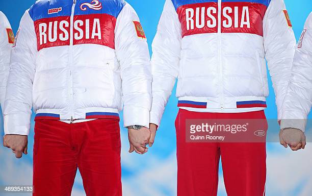 Silver medalists Russia hold hands on the podium during the medal for the Luge Team Relay on day 7 of the Sochi 2014 Winter Olympics at Medals Plaza...