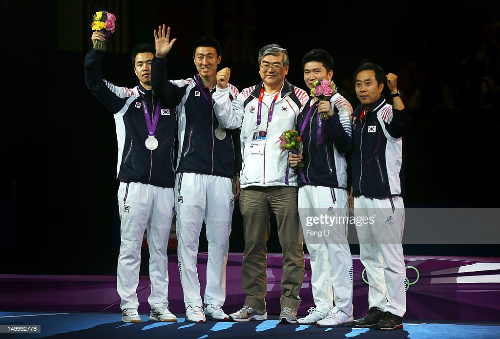 Silver medalists Saehyuk Joo (L), Sang Eun Oh (2nd L), and Seungmin Ryu (2nd R) of Korea celebrate with their coaches on the podium during the medal ceremony for the Men's Team Table Tennis on Day 12 of the London 2012 Olympic Games at ExCeL on August 8, 2012 in London, England.