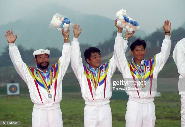 Silver medalists Takayoshi Matsushita Hiroshi Yamamoto and Sadamu Nishikawa of Japan celebrate on the podium at the medal ceremony for the Archery...