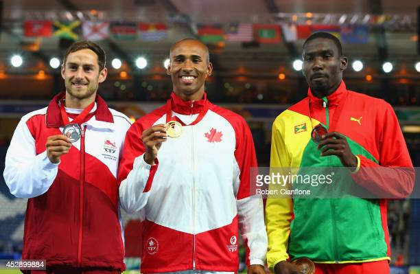 Silver medallist Ashley Bryant of England Gold medallist Damian Warner of Canada and bronze medallist Kurt Felix of Grenada pose on the podium during...