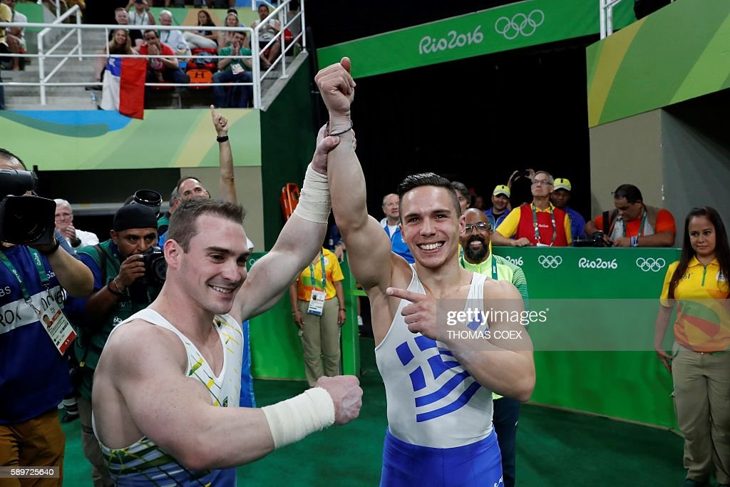 Silver medallist Brazil's Arthur Zanetti and gold medallist Greece's Eleftherios Petrounias celebrate after the men's rings event final of the...