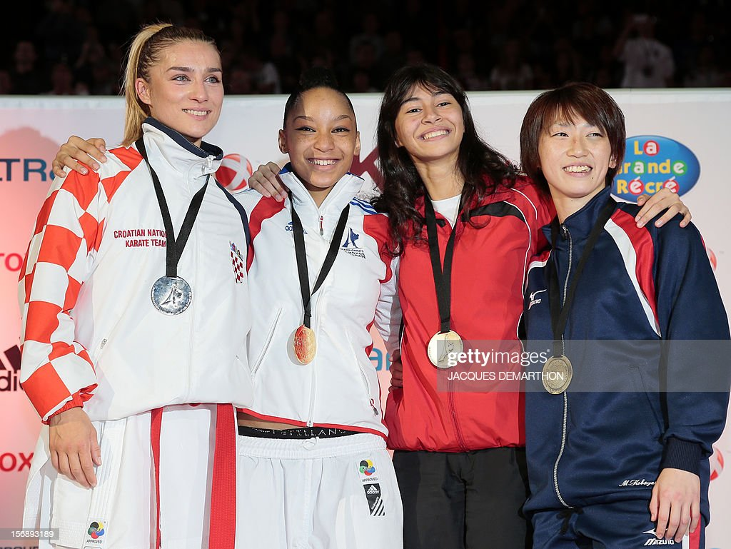 Silver medallist Croatia's Jelena Kovacevic, gold medallist France's Lucie Ignace (C) and bronze medallists Egypt's Yassmin Attia and Japan's Miki Kobayashi pose on the podium with their medals in the Female Kumite under 55Kg category of the world karate championships on November 23, 2012 in Paris. DEMARTHON