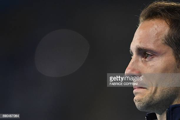 TOPSHOT Silver medallist France's Renaud Lavillenie cries during the medal ceremony for the men's pole vault during the athletics event at the Rio...