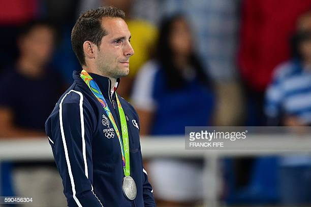 TOPSHOT Silver medallist France's Renaud Lavillenie cries on the podium during the medal ceremony for the men's pole vault during the athletics event...