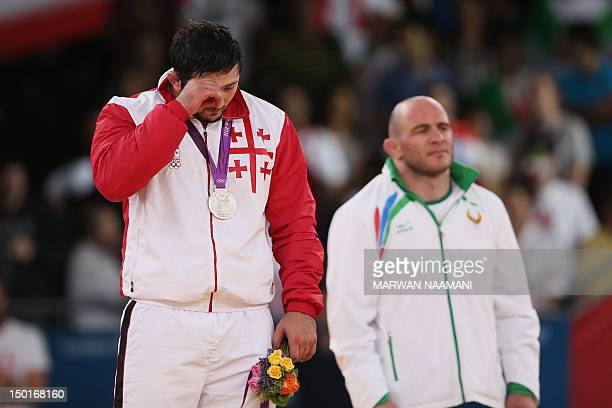 Silver medallist Georgia's Davit Modzmanashvili cries next to gold medallist Uzbekistan's Artur Taymazov on the podium of the Men's 120kg on August...