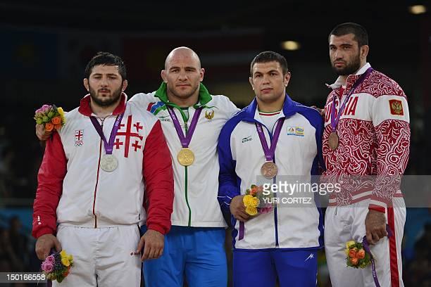 Silver medallist Georgia's Davit Modzmanashvili gold medallist Uzbekistan's Artur Taymazov bronze medallists Iran's Komeil Ghasemi and Russia's...