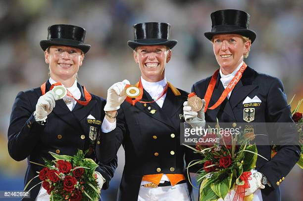 Silver medallist Isabell Werth of Germany gold medallist Anky van Grunsven from the Netherlands and Heike Kemmer of Germany pose on the podium after...