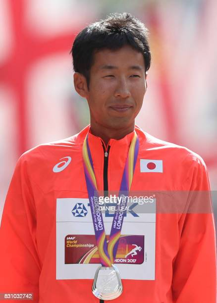 Silver medallist Japan's Hirooki Arai poses on the podium during the victory ceremony for the men's 50km race walk athletics event at the 2017 IAAF...