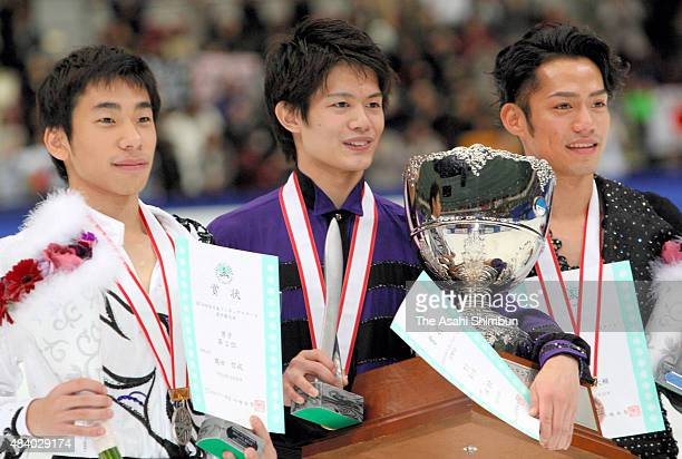 Silver medallist Nobunari Oda gold medallist Takahiko Kozuka and bronze medallist Daisuke Takahashi pose at the medal ceremony for the Men's Singles...