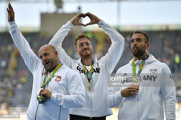 Silver medallist Poland's Piotr Malachowski Gold medallist Germany's Christoph Harting and bronze medallist Germany's Daniel Jasinski celebrate on...