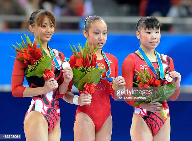 Silver medallist Rie Tanaka gold medallist Huang Qiushuang of China and bronze medallist Momoko Ozawa of Japan pose on the podium at the medal...