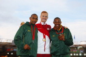 Silver medallist Zarck Visser of South Africa gold medallist Greg Rutherford of England and bronze medallist Rushwahl Samaai of South Africa pose on...