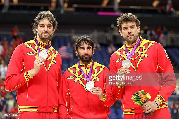 Silver medallists Pau Gasol of Spain and Marc Gasol of Spain pose on the podium with team mate Victor Sada of Spain during the medal ceremony for the...