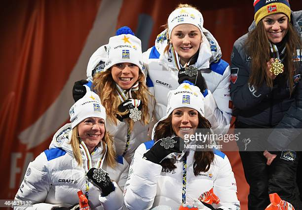 Silver medallists Sofia Bleckur Charlotte Kalla Maria Rydqvist and Stina Nilsson of Sweden pose during the medal ceremony for the Women's 4 x 5km...