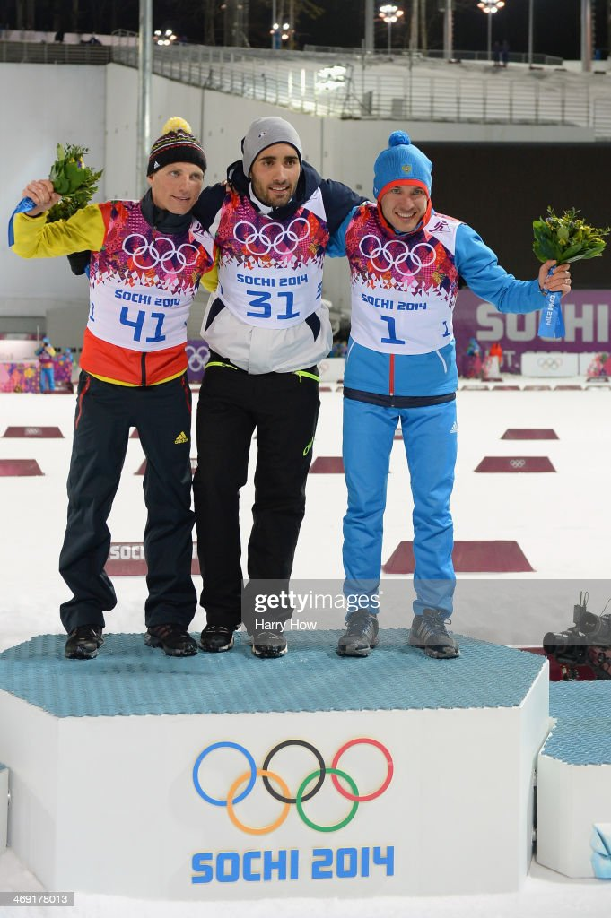 Silver medlaist <a gi-track='captionPersonalityLinkClicked' href=/galleries/search?phrase=Erik+Lesser&family=editorial&specificpeople=6837118 ng-click='$event.stopPropagation()'>Erik Lesser</a> of Germany, gold medalist <a gi-track='captionPersonalityLinkClicked' href=/galleries/search?phrase=Martin+Fourcade&family=editorial&specificpeople=5656850 ng-click='$event.stopPropagation()'>Martin Fourcade</a> of France and bronze medalist <a gi-track='captionPersonalityLinkClicked' href=/galleries/search?phrase=Evgeniy+Garanichev&family=editorial&specificpeople=8772104 ng-click='$event.stopPropagation()'>Evgeniy Garanichev</a> of Russia celebrate oon the podium during the flower ceremony for the Men's Individual 20 km during day six of the Sochi 2014 Winter Olympics at Laura Cross-country Ski & Biathlon Center on February 13, 2014 in Sochi, Russia.