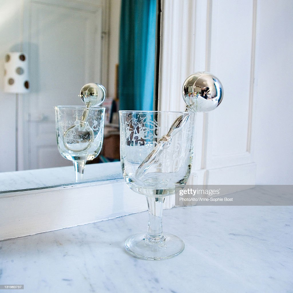 Silver rattle in stemmed glass in front of mirror : Stock Photo