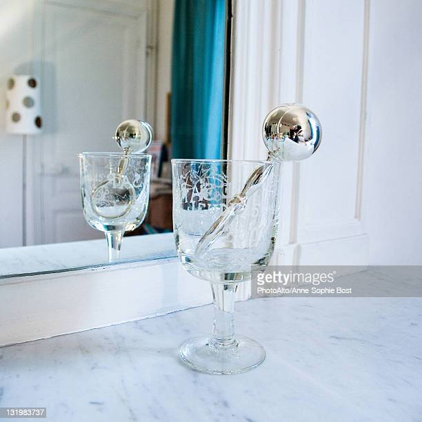 Silver rattle in stemmed glass in front of mirror