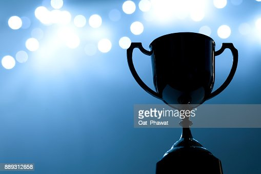 Silver Trophy competition in the dark on the abstract blurred light background with copy space, Blue Tone : Stock Photo