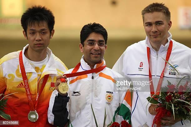 Silver winner Zhu Qinan of China gold winner Abhinav Bindra of India and bronze winner Henri Hakkinen of Finland celebrate with their medals on the...