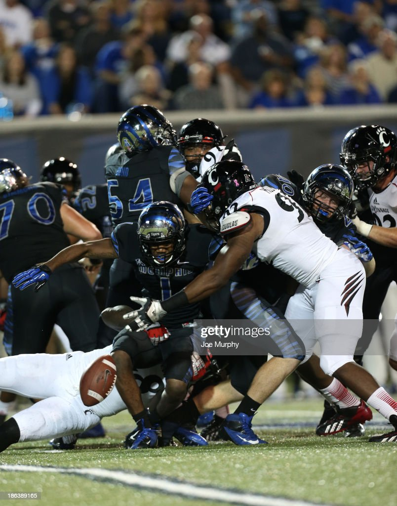 Silverberry Mouhon #92 of the Cincinnati Bearcats forces a fumble by Marquis Warford #1 of the Memphis Tigers on October 30, 2013 at Liberty Bowl Memorial Stadium in Memphis, Tennessee.
