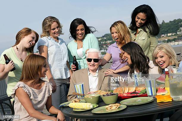 Silver-haired man in sunglasses in the center of young girls