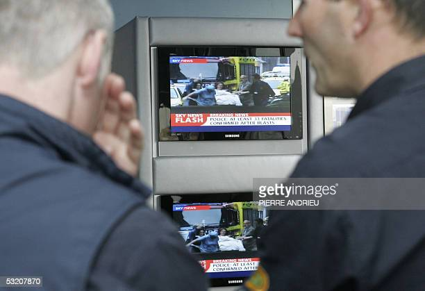 Red Bull team members watch news on TV in the paddocks of the Silverstone racetrack three days before the British Grand Prix 07 July 2005 in...