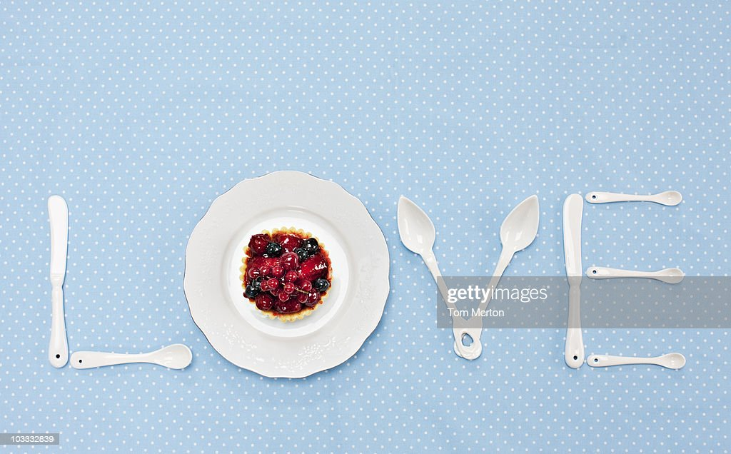 Silverware and plate with tart spelling 'love' on tablecloth : Stock Photo