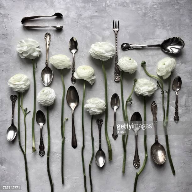 Silverware and white ranunculus flowers
