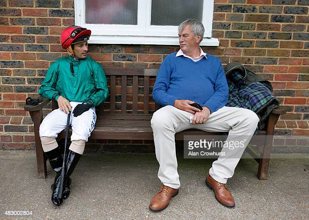 Silvestre De Sousa relaxes on a bench with a member of the public at Brighton racecourse on August 05 2015 in Brighton England