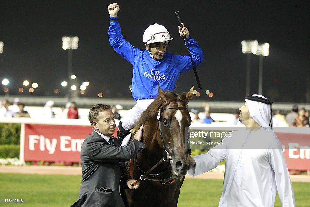 Silvestre De Sousa rides Hunter's Light (Blue Silks, white hat) in race 7, the 10f Group 1 Al Maktoum Challenge Round 3 race, is led into the winner's circle by travelling head lad, Tommy Burns and Godolphin Trainer, Saeed bin Suroor, during Super Saturday at Meydan Racecourse on March 9, 2013 in Dubai, United Arab Emirates.