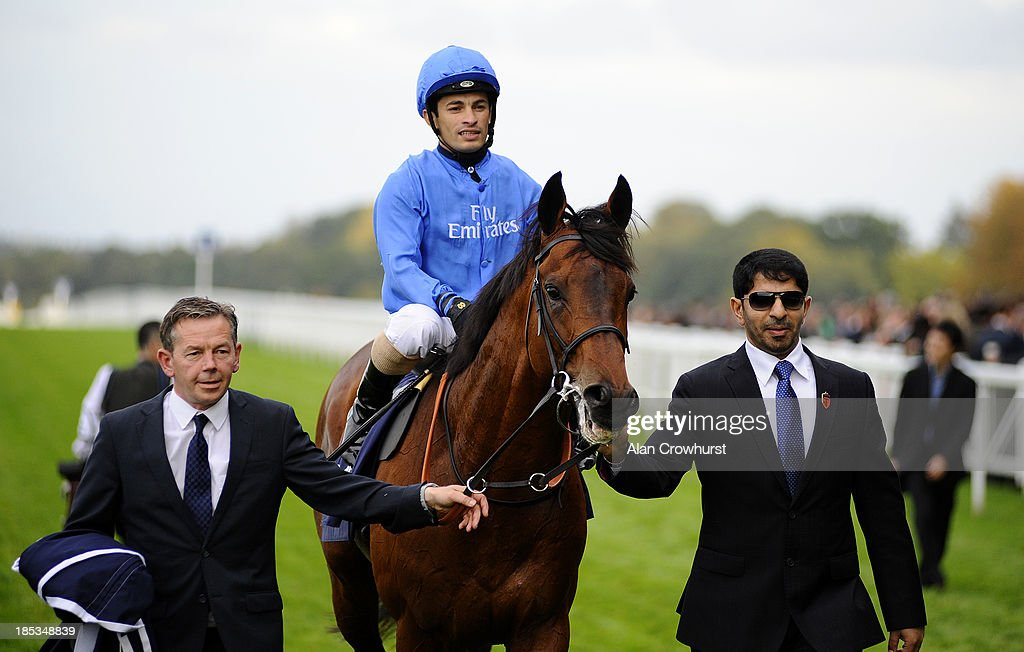 Silvestre De Sousa riding Farhh win The Qipco Champion Stakes is led in by trainer Saeed bin Suroor (R) at Ascot racecourse on October 19, 2013 in Ascot, England.