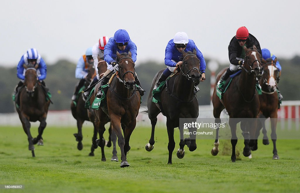 Silvetre De Sousa riding Ihtimal (L) win The Barrett Steel May Hill Stakes at Doncaster racecourse on September 13, 2013 in Doncaster, England.