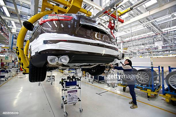 Silvia Fioretti a production line team leader at Maserati SpA works on a Maserati Ghibli luxury automobile as it travels along the production line at...