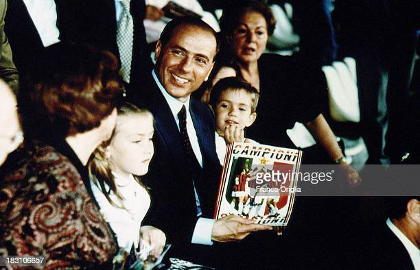 Silvio Berlusconi President of football team AC Milan his mother Rosa Bossi and his children Eleonora and Luigi hold a pennant celebrating the...