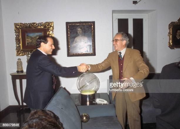 Silvio Berlusconi shakes hand of Massimo Pini the director of IRI