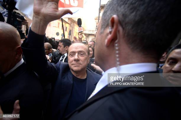 Silvio Berlusconi surrounded by bodyguards waves at his supporters as he arrives at his home in downtown Rome on March 11 2015 Italy's top court on...