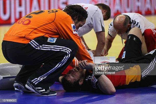 Silvio Heinevetter cares of the injured Michael Haass of Germany during the Men's European Handball Championship second round group one match between...