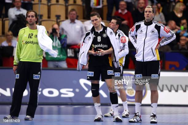 Silvio Heinevetter Sebastian Preiss and Pascal Hens of Germany look dejected after the Men's Handball World Championship Group A match between...
