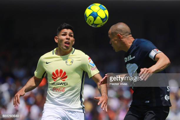Silvio Romero of Americaa struggles for the ball with Dario Veron of Pumas during the 11th round match between Pumas UNAM and America as part of the...