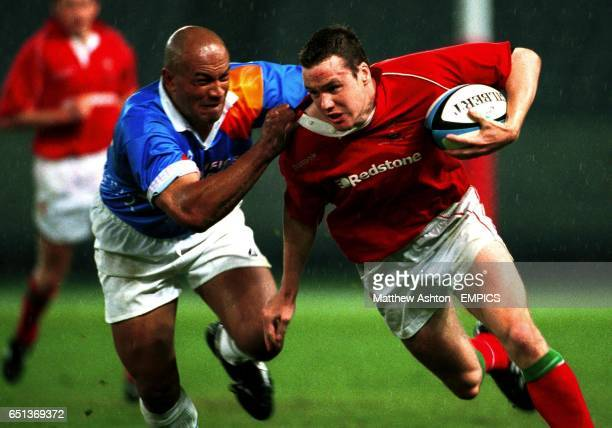 Simana Mafileo of the Pacific Barbarians pulls the shirt of Mark Jones of Wales