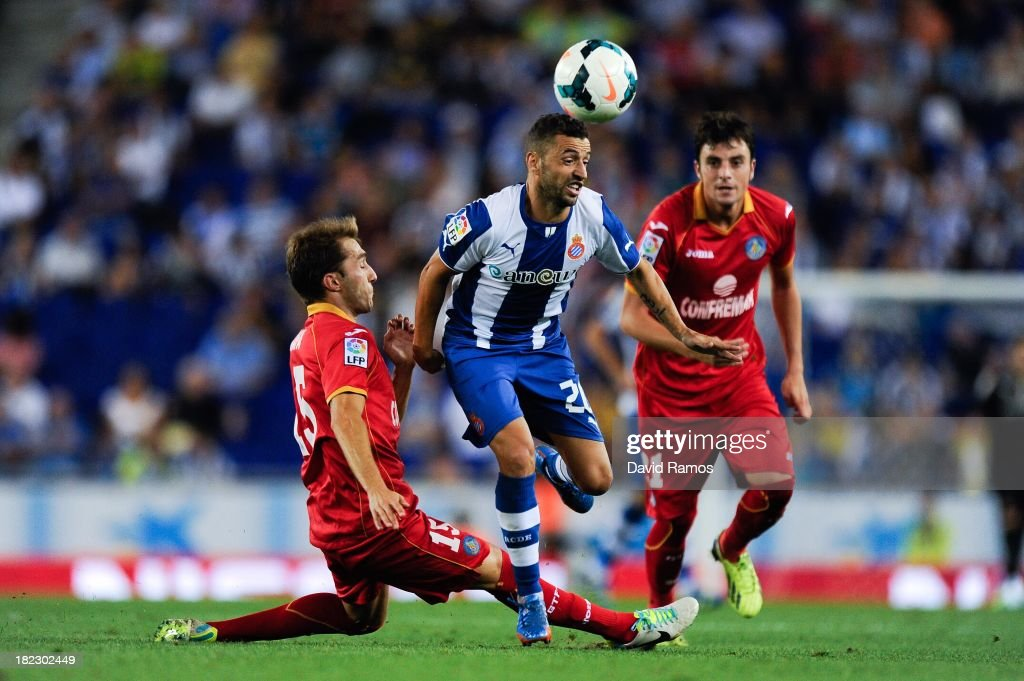 Simao Sabrosa of RCD Espanyol duels for the ball with Rafael Lopez (L) and Michel Madera of Getafe CF during the La Liga match between RCD Espanyol and Getafe CF at Cornella-El Prat Stadium on September 29, 2013 in Barcelona, Spain.